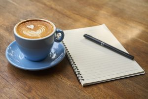 photo of a cup of coffee, a notebook and a pen