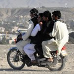 Image of three men on a motorcycle