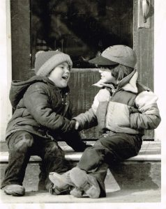 black and white photo of two boys dressed for winter and they are shaking hands